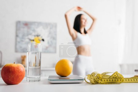 Selective focus of measuring tape, fruits with scales and glass of water on table and sportswoman in kitchen, calorie counting diet