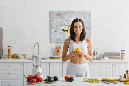 Photo for Smiling sportswoman holding orange near scales, measuring tape and vegetables on kitchen table, calorie counting diet - Royalty Free Image
