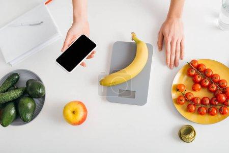 Photo pour Haut de la page Une jeune fille tient un téléphone intelligent pendant qu'elle pèse des bananes sur une table de cuisine, compte des calories - image libre de droit