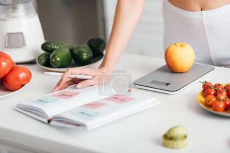 Photo for Selective focus of woman writing calories while weighing apple near fresh vegetables on kitchen table, calorie counting diet - Royalty Free Image