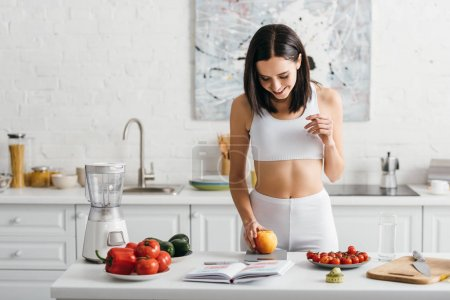 Smiling sportswoman weighing apple near notebook and measuring tape on kitchen table, calorie counting diet