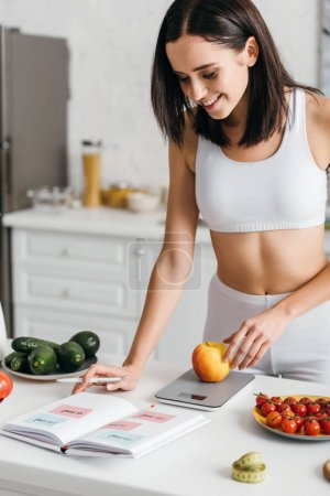 Photo for Selective focus of beautiful smiling sportswoman writing calories while weighing apple on kitchen table, calorie counting diet - Royalty Free Image