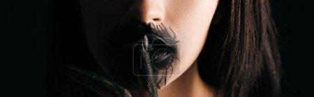 Photo pour Vue panoramique de la femme avec des lèvres peintes en noir et la main montrant geste calme isolé sur noir - image libre de droit