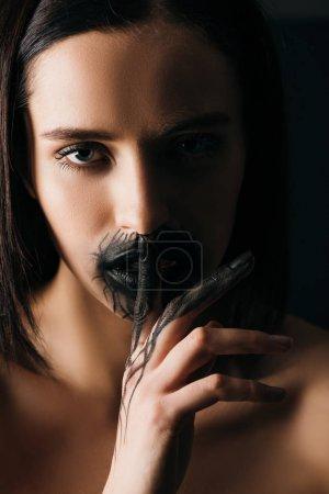 Photo pour Belle femme nue avec main et lèvres peintes en noir montrant un geste de silence et regardant la caméra isolée sur noir - image libre de droit