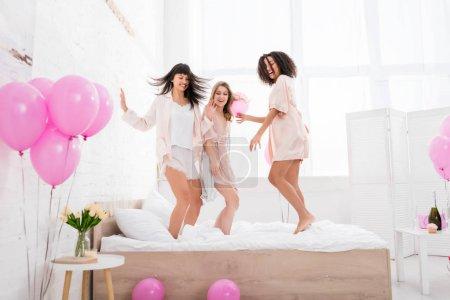 Photo pour Lesbiennes multiethniques émotionnelles sautant sur le lit avec des ballons roses - image libre de droit