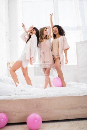 Foto de Feliz multicultural novias saltar en la cama con rosa globos - Imagen libre de derechos