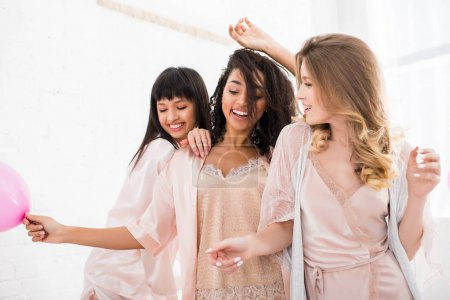Photo for Emotional multiethnic girls in bathrobes dancing on bachelorette party - Royalty Free Image
