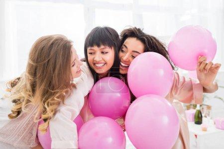 Photo pour Émotionnel multiculturel filles s'amuser avec des ballons roses sur le pajama party - image libre de droit