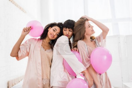 Photo for Attractive multicultural girls having fun with pink balloons in bedroom - Royalty Free Image