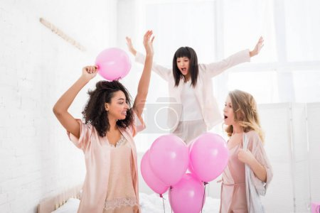 Photo for Attractive happy multicultural girlfriends dancing and jumping on bed with pink balloons  for bachelorette party - Royalty Free Image