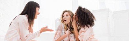 Foto de Foto panorámica de chicas multiculturales chocadas susurrando y chispeando sobre el partido pajama. - Imagen libre de derechos