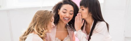 Photo for Panoramic shot of smiling multicultural girlfriends whispering and gossiping on pajama party - Royalty Free Image