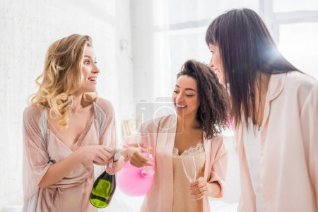 Photo for Happy multicultural girls opening bottle of champagne on bachelorette party - Royalty Free Image