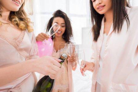 Photo pour Des jeunes filles multiethniques attirantes ouvrent une bouteille de champagne lors d'une bachelorette - image libre de droit