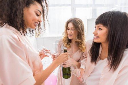 Foto de Sonrientes muchachas multiétnicas que abren una botella de champán en el partido bachelorette. - Imagen libre de derechos