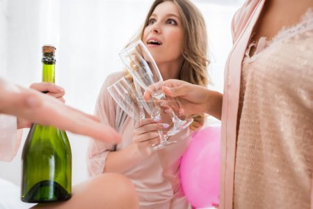Photo for Emotional girlfriends holding glasses while opening bottle of champagne on bachelorette party - Royalty Free Image
