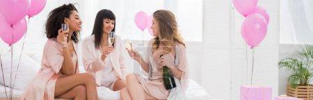 Photo pour Plan panoramique de filles multiethniques heureuses avec champagne parlant sur enterrement de vie de jeune fille avec ballons - image libre de droit