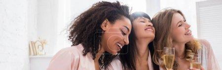 Photo pour Photo panoramique de joyeuses amies multiculturelles s'amusant et tenant des verres de champagne lors d'une fête de pajama - image libre de droit