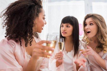 Photo pour Surpris copines multiethniques avec des verres de champagne parler sur pyjama partie - image libre de droit