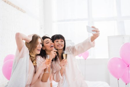 Photo for Attractive multicultural girls with glasses of champagne taking selfie on smartphone during pajama party - Royalty Free Image