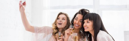 Photo for Panoramic shot of smiling multiethnic girls with glasses of champagne taking selfie on smartphone during pajama party - Royalty Free Image