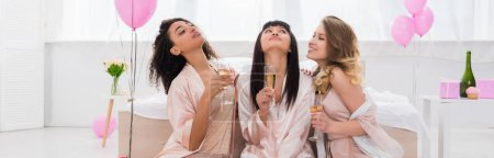 Photo for Panoramic shot of positive multicultural girlfriends having fun and holding champagne glasses on pajama party with pink balloons - Royalty Free Image