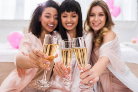 Photo for Selective focus of smiling multicultural girls clinking with glasses of champagne on bachelorette party - Royalty Free Image