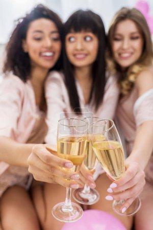 Photo pour Focalisation sélective des filles multiculturelles brandissant des verres de champagne lors d'une bachelorette - image libre de droit