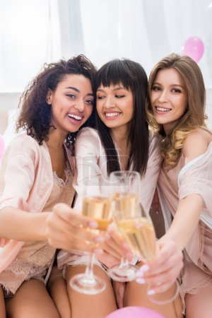 Photo for Selective focus of happy multicultural girls clinking with glasses of champagne on bachelorette party - Royalty Free Image