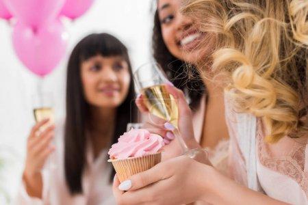 Photo pour Foyer sélectif de filles multiculturelles heureuses s'amuser avec du champagne et cupcake pendant la fête de célibataire - image libre de droit