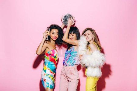 Photo pour Joyeuses copines multiculturelles avec champagne et bal disco dansant sur rose - image libre de droit