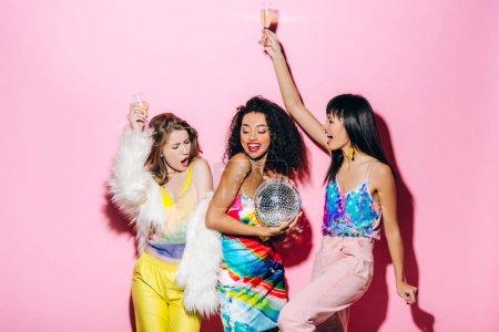 Photo pour Excité copines multiculturelles avec champagne et boule disco s'amuser sur rose - image libre de droit