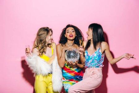 Photo pour Joyeuses filles multiethniques avec champagne et bal disco dansant sur rose - image libre de droit