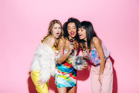 Photo for Beautiful multiethnic girls holding disco ball and champagne while singing karaoke with microphone on pink - Royalty Free Image