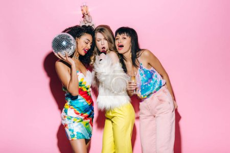 Photo for Emotional multiethnic girls holding champagne glasses and disco ball while singing with microphone on pink - Royalty Free Image
