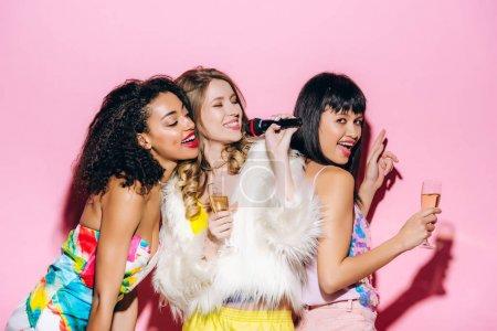 Photo pour Gaies copines multiculturelles tenant des verres de champagne et boule disco tout en chantant avec microphone sur rose - image libre de droit