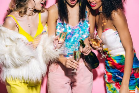 Photo for Cropped view of emotional multicultural girlfriends pouring champagne from bottle into glasses on pink - Royalty Free Image