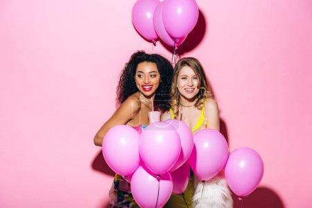 Photo pour Copines souriantes multiculturelles tenant milkshakes sur rose avec des ballons - image libre de droit