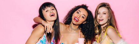 Photo for Panoramic shot of happy fashionable multiethnic girls holding glasses with milkshakes on pink - Royalty Free Image