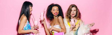 Photo for Panoramic shot of cheerful stylish multiethnic girlfriends drinking milkshakes on pink - Royalty Free Image