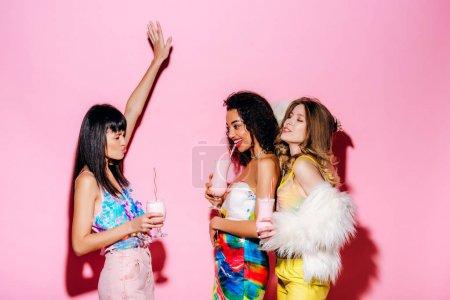 Photo pour Émotionnel élégant multiethnique filles boire milkshakes sur rose - image libre de droit