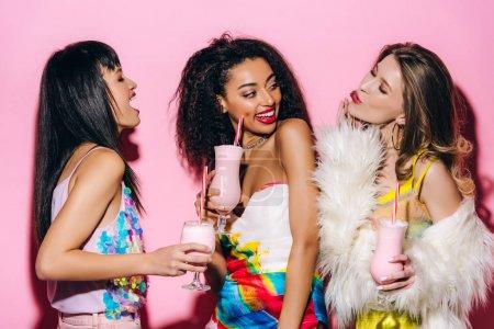 Photo pour Heureux élégant multiethnique filles boire milkshakes sur rose - image libre de droit