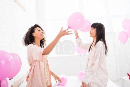 Foto de Chicas emocionantes y multiculturales en albornoces con globos rosados en el partido bachelorette. - Imagen libre de derechos