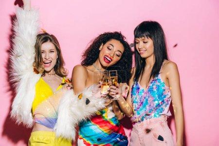 Foto de Alegre multicultural niñas divertirse con copas de champán en rosa con confeti - Imagen libre de derechos