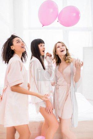 Foto de Jovencitas multiculturales emocionantes divirtiéndose con globos rosas en el dormitorio. - Imagen libre de derechos