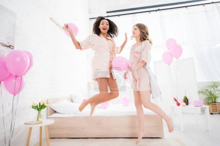 Photo for Excited multiethnic girlfriends in bathrobes jumping with pink balloons on pajama party - Royalty Free Image