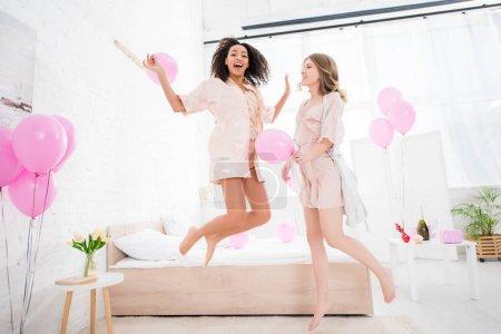 Photo pour Amies multiethniques excitées en peignoirs de bain sautant avec des ballons roses sur une fête de pajama - image libre de droit