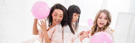 Photo pour Photo panoramique de filles multiculturelles s'amusant avec des ballons roses en chambre à coucher - image libre de droit