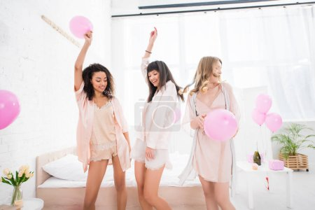 Photo for Happy multicultural girls dancing with pink balloons in bedroom - Royalty Free Image
