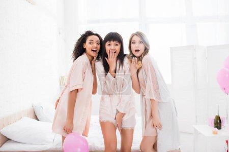 Foto de Shock multicultural girls in nightwear in bedroom with pink balloons. - Imagen libre de derechos